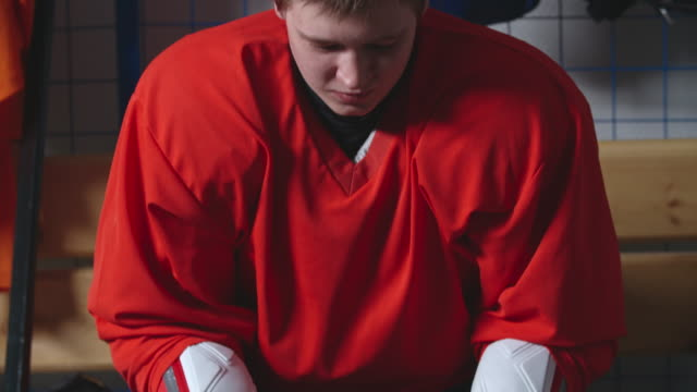 determined looking female ice hockey player putting helmet on - helmet stock videos & royalty-free footage
