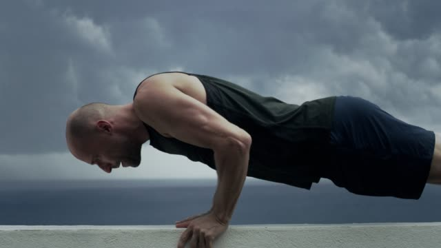determined man doing push ups by the sea - coastal feature stock videos & royalty-free footage