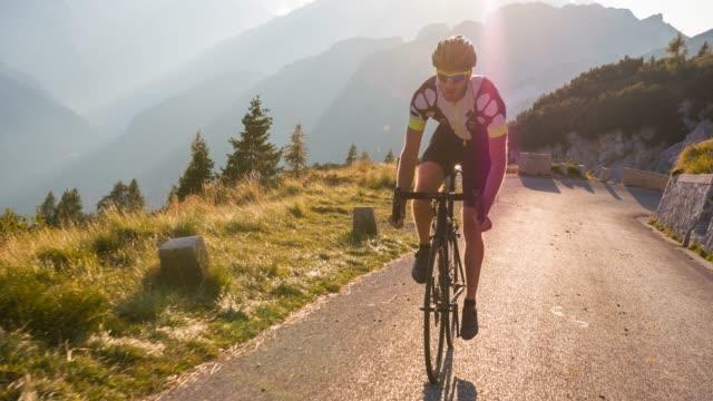 上り坂の曲がりくねった山道に乗ってプロの男性サイクリストを決定 - アウトドア点の映像素材/bロール