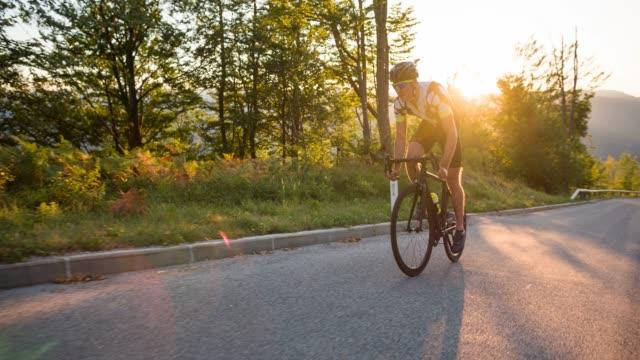 vidéos et rushes de cycliste routier professionnel déterminé approchant la fin de la course sportive, à vélo en montée - qui monte
