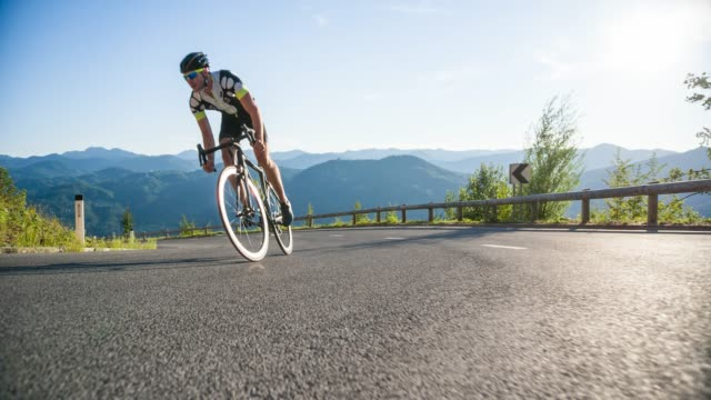 determined professional road cyclist pedaling uphill standing up - uphill stock videos & royalty-free footage