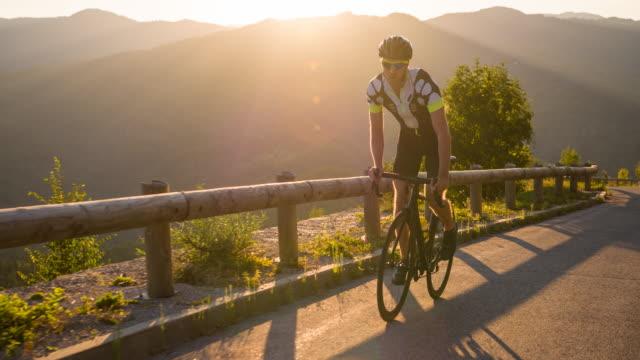 vídeos de stock, filmes e b-roll de ciclista de estrada determinado ciclismo em subida - colina acima