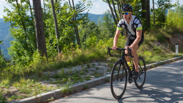 determined road cyclist cycling uphill - dedication stock videos and b-roll footage