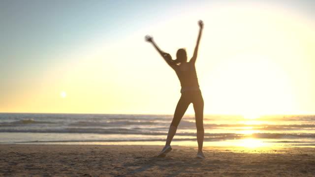 determined woman doing cartwheel on shore - cartwheel stock videos & royalty-free footage