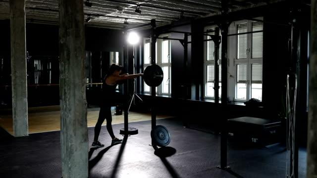 vidéos et rushes de femme déterminée squat avec haltères en gym - musclé