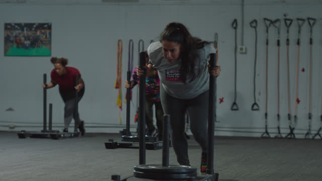 ls of determined woman using push sled to train strength and endurance - dedication stock videos & royalty-free footage