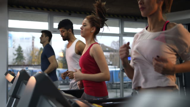 determined young people running on treadmill in a gym. - treadmill stock videos & royalty-free footage