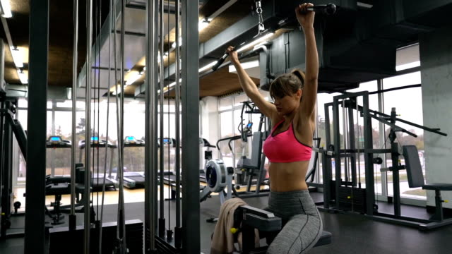 determined young woman exercising on lateral-pull down weight machine in a health club. - lateral pull down weights stock videos & royalty-free footage