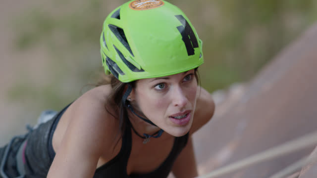 slo mo. determined young woman looks up as she climbs steep rock face on moab adventure. - rock climbing stock videos & royalty-free footage