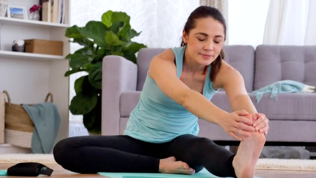 Determined young woman stretches muscles  before working out at home