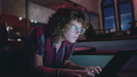 stockvideo's en b-roll-footage met cu determined, young woman yawns as she works on her laptop through the night - after work