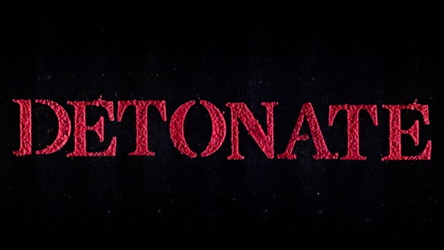 Detonate written in red powder exploding in slow motion.