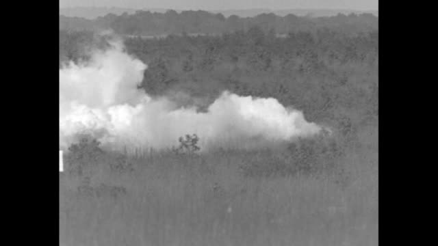 vídeos y material grabado en eventos de stock de cu detonator as army soldier pushes plunger / vs explosions in field with white smoke billowing in clouds / army personnel load field guns and turn... - explosivo