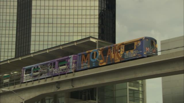 a detroit commuter train on an elevated railway passes the general motors building. - högbana bildbanksvideor och videomaterial från bakom kulisserna
