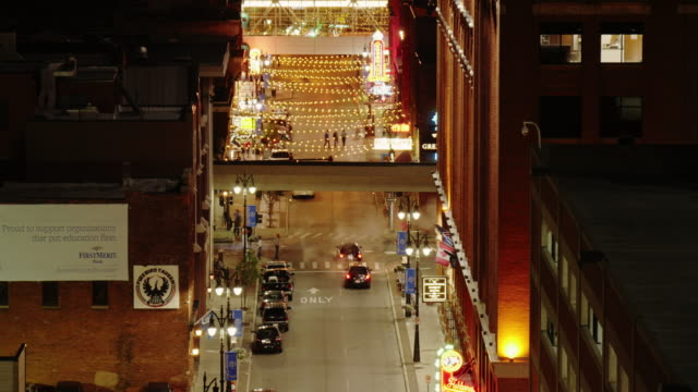 detroit greektown in downtown at night. wide time lapse shot from above with people mover crossing - spoonfilm stock-videos und b-roll-filmmaterial