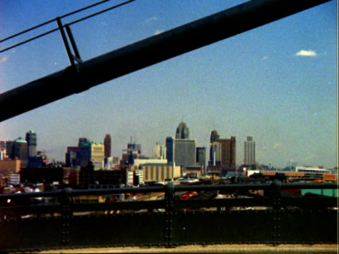 detroit skyline as viewed from ambassador bridge a portion of which is visible / detroit skyline rail yard in foreground pan right across detroit... - ontario kanada stock-videos und b-roll-filmmaterial