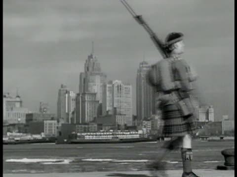 detroit skyline from canada stationary ferry in detroit river canadian highlander guard in kilt w/ rifle patrolling fg ls 'peace bridge' cars... - detroit river stock-videos und b-roll-filmmaterial