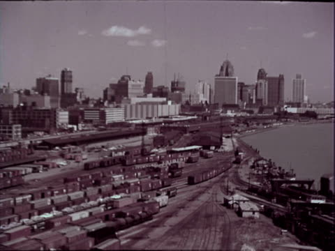 detroit skyline rail yard in fg tall buildings in bg pan right across detroit river to windsor ontario canada / detroit skyline as viewed from... - デトロイト点の映像素材/bロール