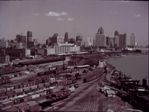 vídeos de stock, filmes e b-roll de detroit skyline rail yard in fg tall buildings in bg pan right across detroit river to windsor ontario canada / detroit skyline as viewed from... - 1963
