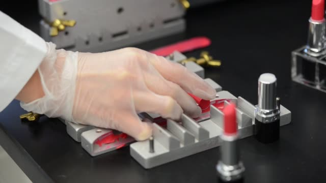 vidéos et rushes de development chemist removes lipsticks from a mold in this arranged photographed at the avon products inc. research and development facility in... - rouge à lèvres