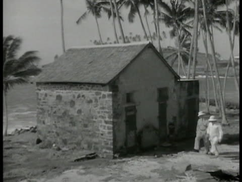 vidéos et rushes de devil's island . two men walking past small stone house in penal colony. graves w/ headstones on hill overlooking sea. saint laurent du maroni: camp... - dom tom