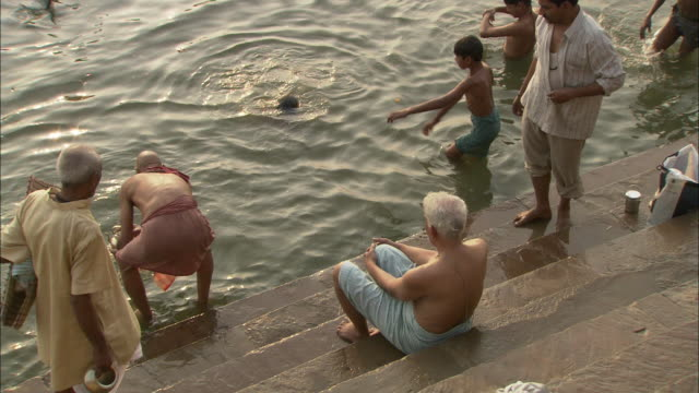 a devotee dips an urn and a seashell into the ganges as other devotees bathe or wait their turns. - seashell stock videos & royalty-free footage
