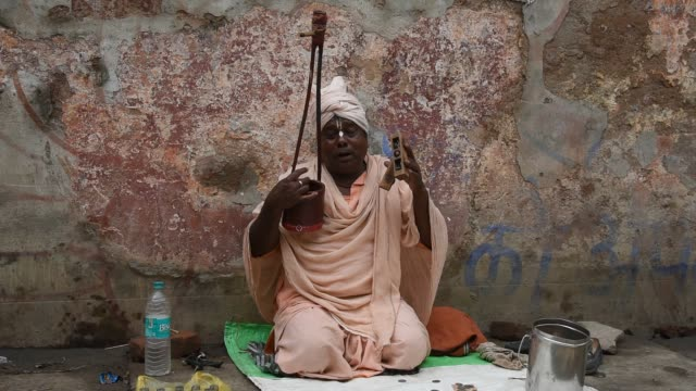 stockvideo's en b-roll-footage met devotee playing kirtan on the street of vrindavan - chanten