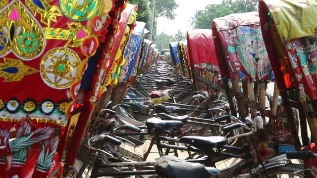 dhaka 21 june 2018 during eid vacation a line of tricycle rickshaws is parked on a roadside at dhaka this year more than six and half million people... - tricycle stock videos & royalty-free footage