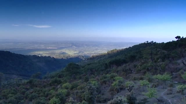 dharamsala landscapes. pan-left across forested dhauladhar mountains and the kangra valley below. - 東点の映像素材/bロール
