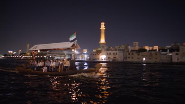 stockvideo's en b-roll-footage met dhow boat crosses dubai creek at night - nationale vlag