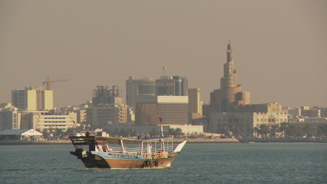 WS Dhow sailing in Doha Bay, city skyline  in background / Doha, Qatar