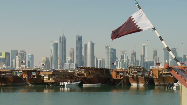 vídeos de stock e filmes b-roll de ws zo dhows moored in marina with city skyline in background / doha, qatar - catar