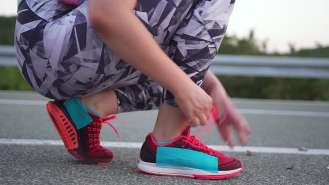 diabetic woman tying up her sports shoe and running - type 1 diabetes stock videos & royalty-free footage