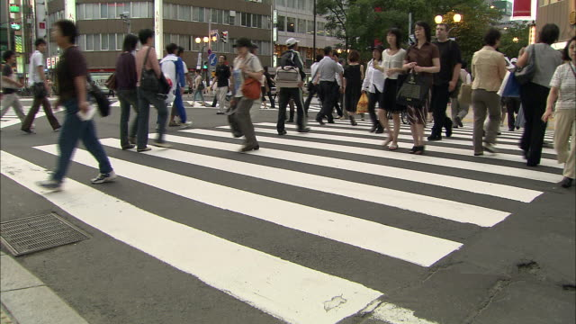 diagonal crosswalk in downtown in sapporo city. shoppers cross the crosswalk. wide and long shot. civic life. the city of winter olympics in 1972. a... - segnale per macchine e pedoni video stock e b–roll