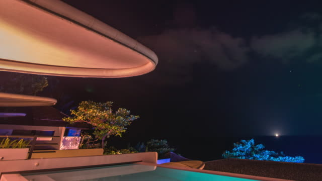 diagonal tilt up time-lapse night scenery of illuminating pool villa in thailand - infinity pool stock videos & royalty-free footage