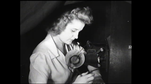 dials turning on machinery and woman taking notes while looking at something off camera - 1940 1949 video stock e b–roll