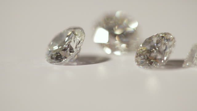 a diamond is placed amongst other diamonds on a surface using tweezers. - ダイヤモンド点の映像素材/bロール