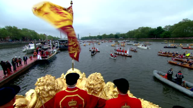vidéos et rushes de 1430 1500 queen and prince philip watching passing boats / boat decorated with union jack flags as spurts water from back in salute / queen watching... - duc d'edimbourg