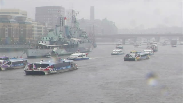 diamond jubilee pageant 2012: 17.30 - 17.45; england: london: river thames: tower bridge: ext / rain boats along river pageant /queen elizabeth,... - fluss themse stock-videos und b-roll-filmmaterial