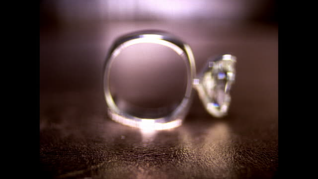 cu sf diamond ring in square silver band reflecting light on tabletop / new york, usa - argentato video stock e b–roll