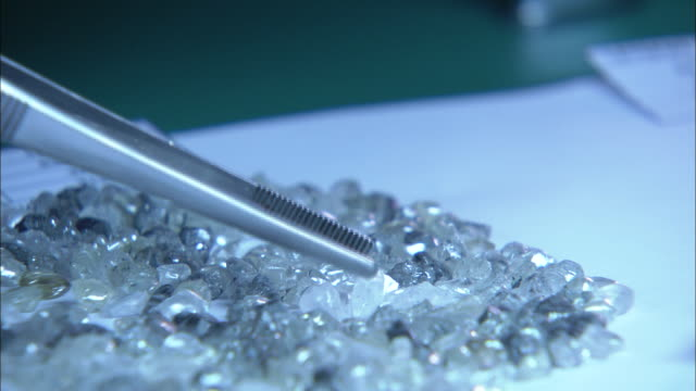 a diamond sorter lifts diamonds with tweezers in south africa. - precious gem stock videos & royalty-free footage