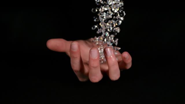 vidéos et rushes de diamonds falling into hand against black background, slow motion 4k - attraper