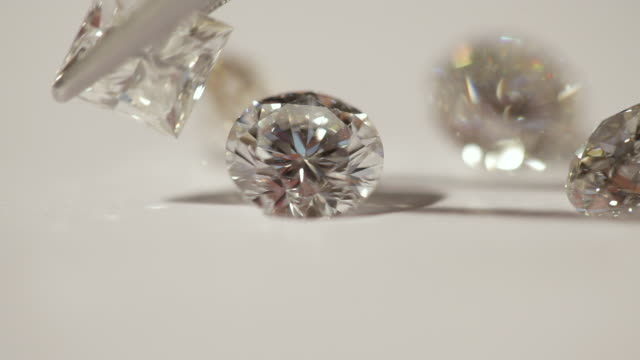 diamonds twinkling in moving light are rearranged with tweezers. - expense stock videos and b-roll footage