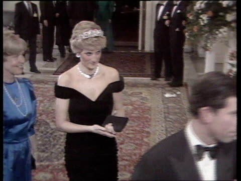 Part 5 T08118701 Arrival at German banquet WEST GERMANY Bonn Diana following Prince Charles in black evening dress playfully taps back of her tiara...