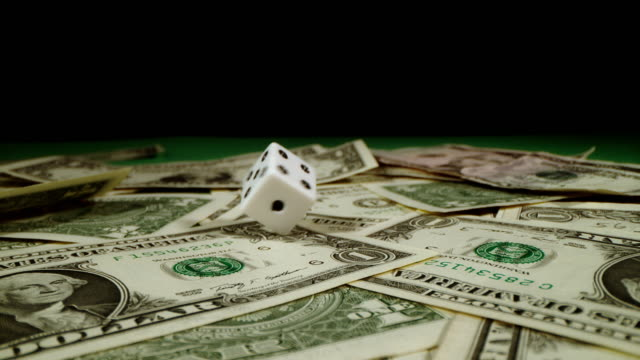 slo mo dice spinning on dollars - dice stock videos & royalty-free footage