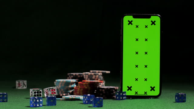 vídeos de stock e filmes b-roll de dices falling near smart phone with green screen, gaming tokens, online casino application, chance to win - poker