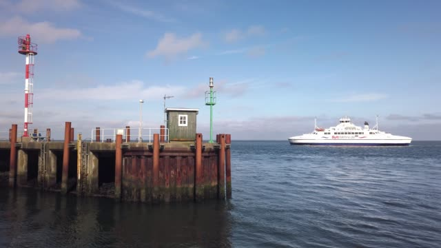 die syltfähre verlässt den hafen von list auf der nordseeinsel sylt bei sonnenschein und wolkenlosem, blauen himmel. - tina terras michael walter stock-videos und b-roll-filmmaterial