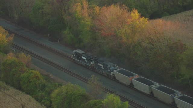 MS AERIAL ZI Diesel coal train traveling on tracks on railroad through rural farmland / Pennsylvania, United States