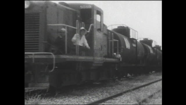 a diesel locomotive pulls a freight train of tanker cars and a boxcar. - locomotive点の映像素材/bロール
