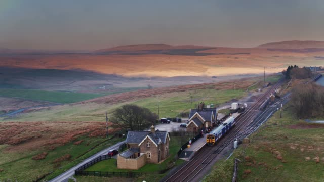 diesel passenger train arriving in ribblehead, north yorkshire - drone shot - scena rurale video stock e b–roll